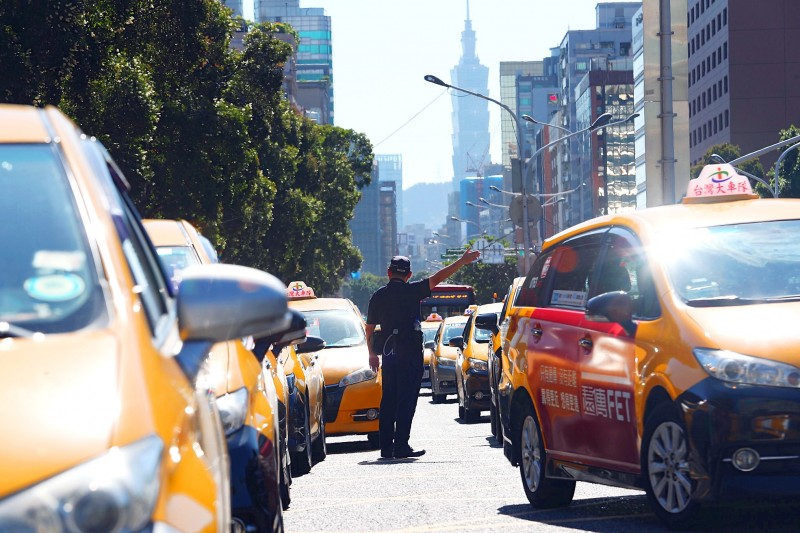 A police officer tries to direct traffic yesterday as hundreds of taxi drivers drive slowly around the Executive Yuan to protest the extension of a grace period for Uber drivers to take the taxi driver's exam. Photo: CNA
