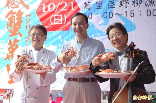 新北市長朱立倫(中)、美食家梁幼祥(左)及大提琴家張正傑(右),在2012年10月時促銷新鮮美味的萬里蟹。(資料照,記者李信宏攝)