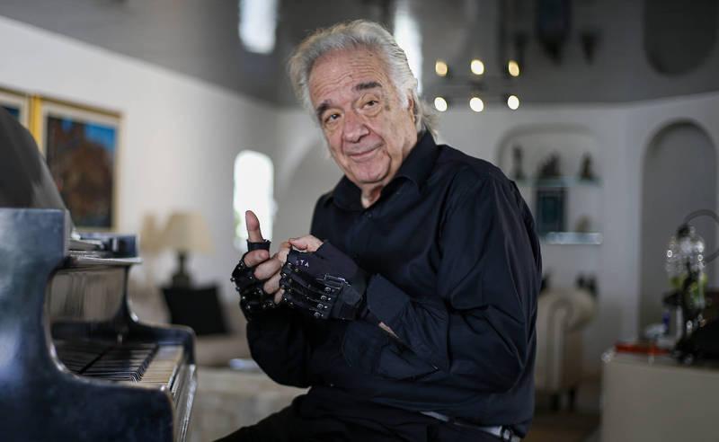 鋼琴大師João Carlos Martins戴上特製手套重拾琴藝。(法新社)