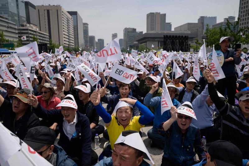 週三有大量不滿生計被共乘壓迫的南韓計程車司機,舉著印有標語的旗幟在光化門廣場示威抗議,要求共乘服務APP「TADA」停止運營。(法新社)