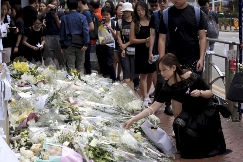 今日有眾多身穿黑衣的港人,至事發現場獻上白花,以悼念昨日墜樓的「黃衣人」(美聯社)