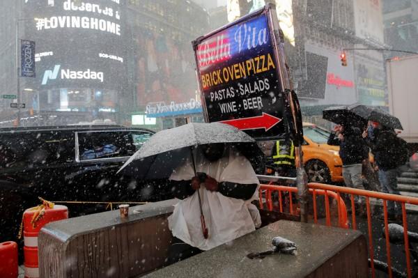 許多民眾撐傘在雨中漫步,喝熱飲取暖。(路透)
