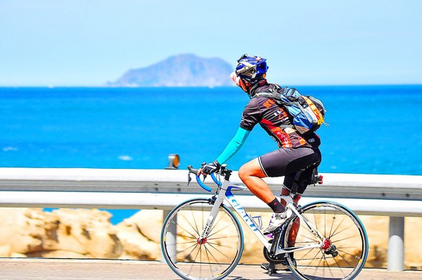A cyclist in Yilan County looks toward Turtle Island, also known as Gueishan Island, in an undated photograph. Photo courtesy of the Tourism Bureau