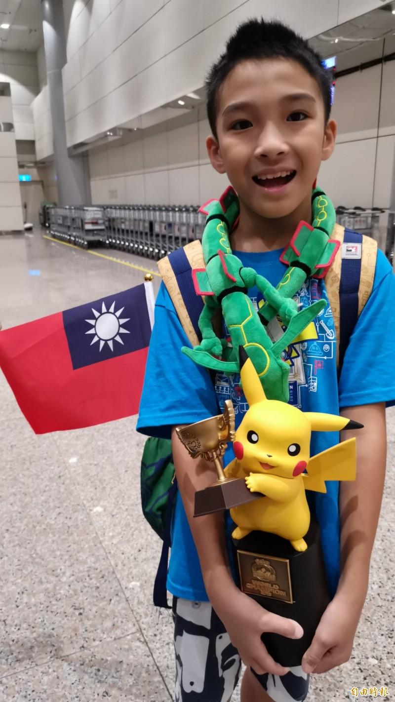 吳比參加世界競標賽兒童組冠軍的獎盃,脖子上掛的是他的幸運寵物寶可夢角色「裂空坐」,背包的小國旗陪著他走完這次的比賽。(記者姚介修攝)