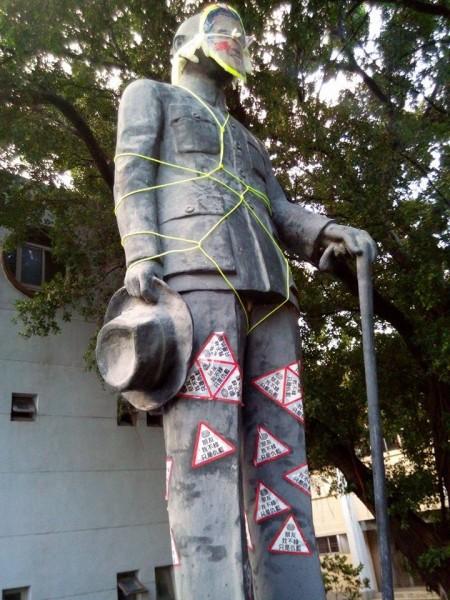 銅像臉部除了被貼上馬英九臉部的照片外,身體也被捆著黃線。(圖片取自pket67網友八卦版的發文)
