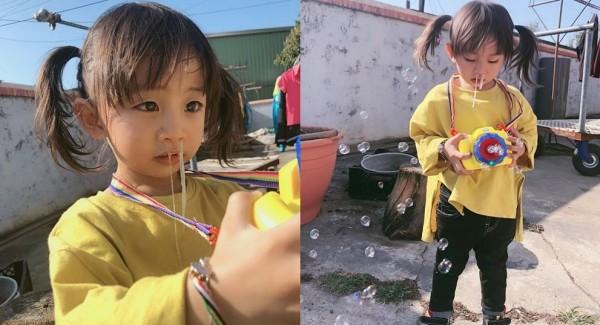 女童不顧自己流鼻涕,繼續玩玩具相機。(民眾提供)