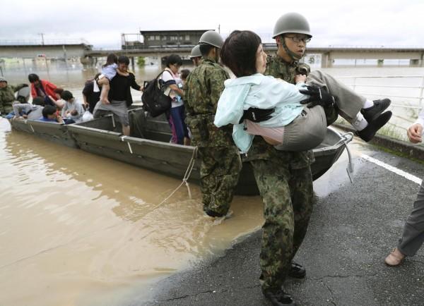一名自衛隊員抱著災民前進。(路透)