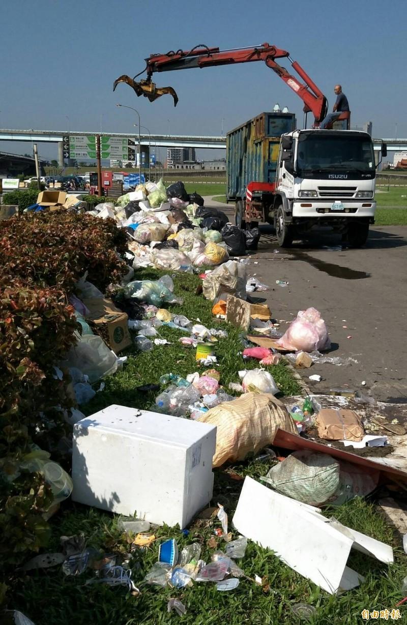 新北市高灘處出動人力、吊車清運造勢後留下的垃圾。(記者劉信德攝)