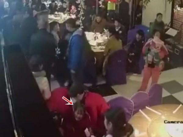 女服務生(箭頭處)被打到倒地。(圖擷自網路)