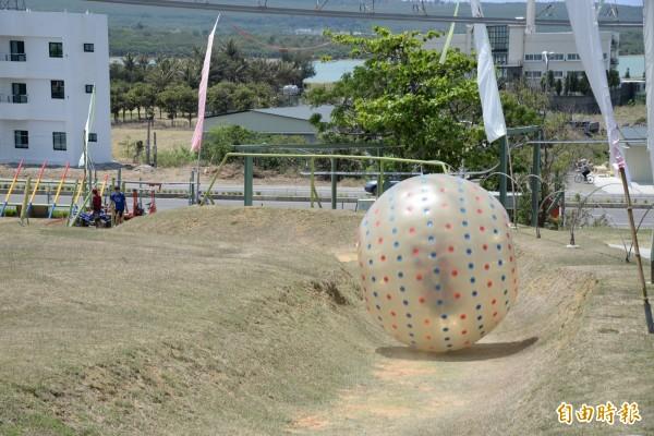 隨著草地飛球從上坡一路向下滾動,讓人轉得暈頭轉向、驚聲尖叫。(記者許麗娟攝)