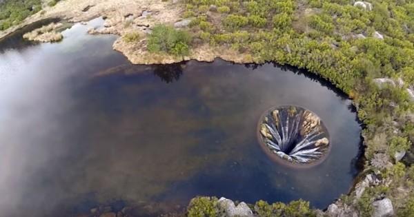 一群葡萄牙當地青年玩無人機時,發現湖面上有一個大洞,水從圓洞邊緣流入,奇景引發討論。(圖片擷取自YouTube)