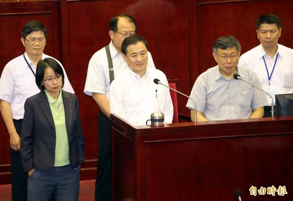 台北市議會日前市政總質詢,台北市長柯文哲(前排右)出席備詢。前排中為副市長陳景峻,前排左為台北農產公司總經理吳音寧,眾人表情都相當嚴肅。(資料照)