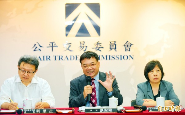 Fair Trade Commission commissioner Hong Tsai-lung, center, speaks at a news conference in Taipei yesterday flanked by Department of Manufacturing Industry Competition Director Chang En-sheng, left, and Department of Legal Affairs Director Wu Tsui-feng.
