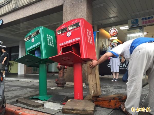 工作人員利用千斤頂工具,把郵筒給歪回來。(記者林煙婷攝)