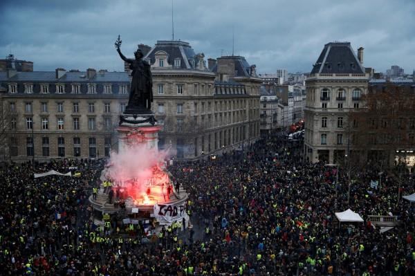 法國巴黎8日「黃背心」運動,整個巴黎街頭陷激戰,警方裝甲車對峙示威者。(路透)