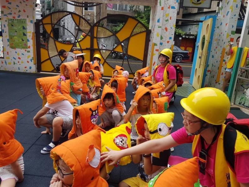幼童戴著「小橘帽」防災頭套,聽著老師指令依序排隊前進,進行地震避難疏散演練。(資料照,台北市教育局提供)