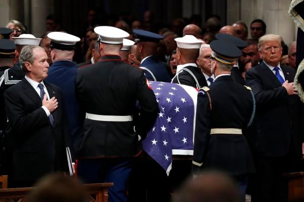 喪禮結束,老布希總統移靈時,前總統小布希(左)、現任總統川普(右)等人都起立致敬(法新社)