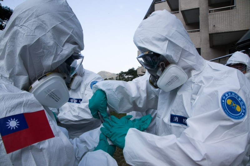 圖為我國軍方人員著裝準備對撤僑回台的隔離處進行衛生處理。(歐新社)