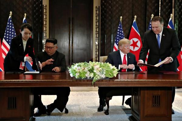金正恩與川普昨下午共同簽署文件時,金與正在一旁協助,並遞上金正恩專用的鋼筆。(路透)