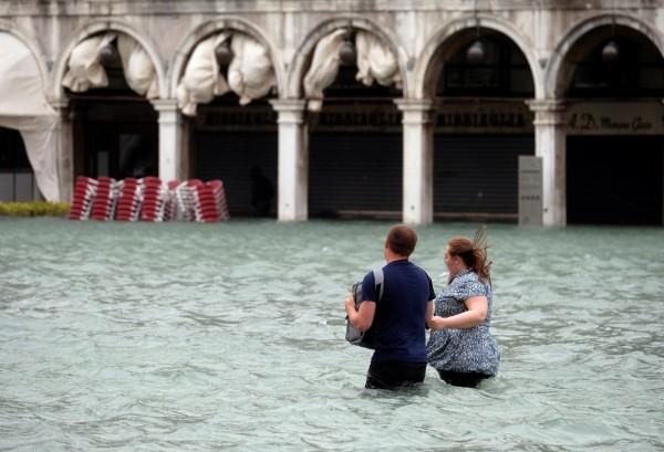 威尼斯逾7成土地被水淹,民眾紛紛涉水而行。(路透)