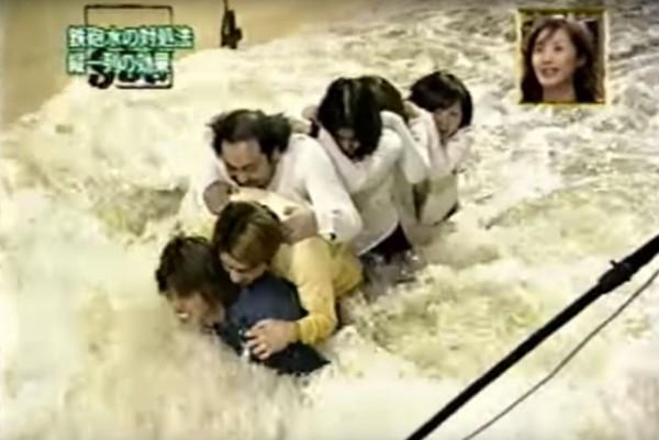 最後讓最有力的男子站在直線隊伍的前方承擔衝擊力,後面跟著的民眾緊緊拉著前一個人,結果眾人順利挺過洪水。(圖擷自Youtube)