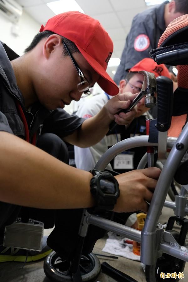 雖是工業高校生,但維修輪椅專注且專業。(記者陳炳宏攝)