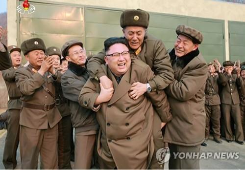 新型高推進力火箭引擎測試成功後,金正恩開心將功臣扛在背上,背上的國防科學技術員則激動的狂掉眼淚。(圖擷自韓聯社)