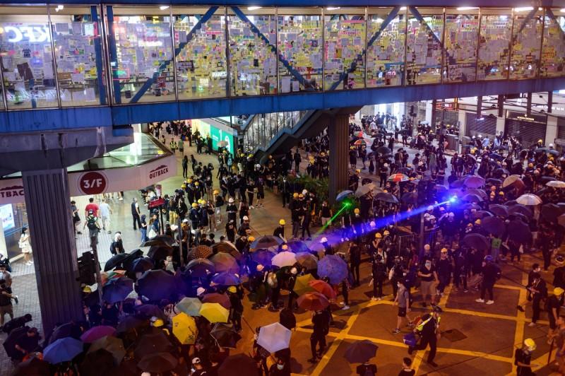 香港抗爭現場因雷射光四散而產生了神奇、科幻般的未來場景,但香港人所必須面對的現實完全不「夢幻」。(法新社)