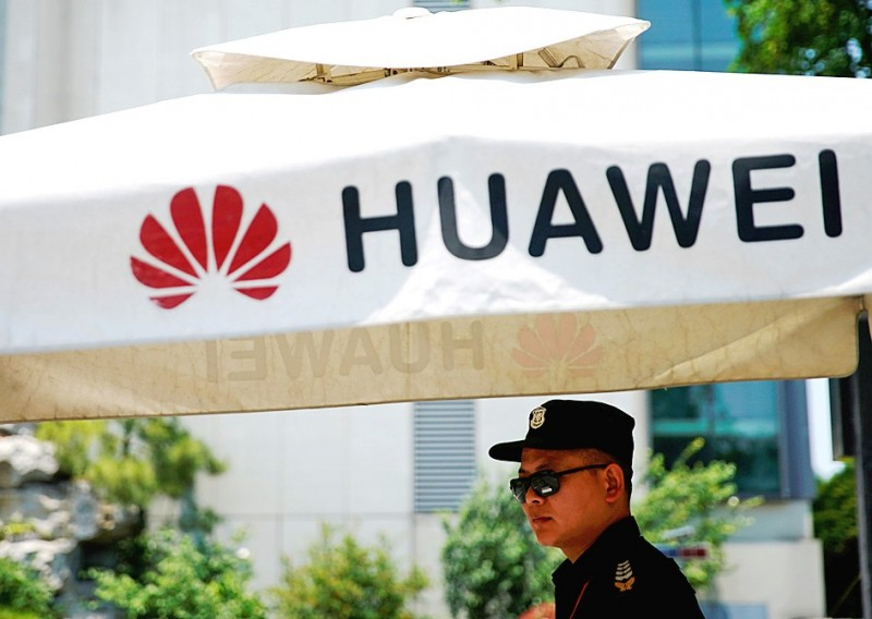 A security guard keeps watch from under a Huawei Technologies Co umbrella at the company's Shanghai Research Center in China yesterday. Photo: Reuters