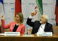 歐盟外交政策首長茉格里尼(左)表示歐盟決定繼續留在協議,並呼籲國際社會繼續執行協議。旁邊是伊朗外交部長(右)(歐新社)
