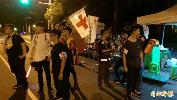 中華緊急救護技術員協會人員抬著擔架在濟南路側門待命。(記者蔡穎攝)
