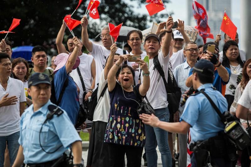 香港議員何君堯與「香港政研會」等親中團體,今日舉行「撐警集會」,許多到場採訪的媒體,遭撐警活動人士惡意辱罵及攻擊,香港記者協會與香港攝影記者協會發表聯合聲明,嚴厲反對踐踏新聞專業,並譴責傷害記者的行為。圖為高舉中國國旗的撐警人士。(法新社)