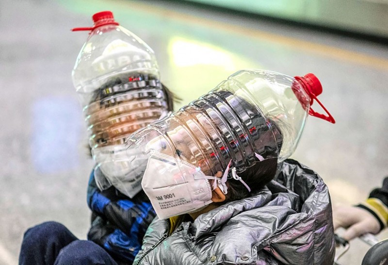 Boys wearing masks, gloves and modified water bottles sit on a cart at the airport arrival terminal in Guangzhou, China, on Feb. 1. Photo: EPA-EFE