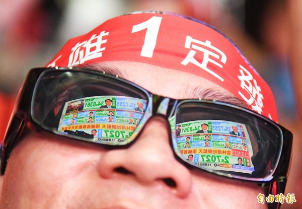 Election results showing that Chinese Nationalist Party (KMT) Kaohsiung mayoral candidate Han Kuo-yu leads the race are mirrored in the sunglasses of a supporter outside Han's campaign headquarters in Kaohsiung yesterday. Photo: CNA