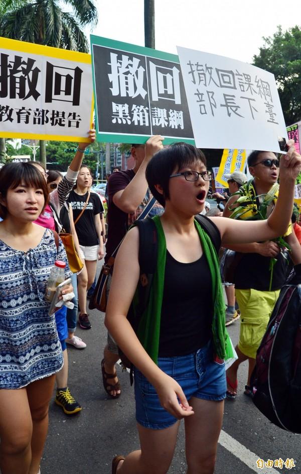 遊行民眾手持標語,齊聲大喊「挺學生護民主!」並要求教育部長吳思華下台。(記者王藝菘攝)
