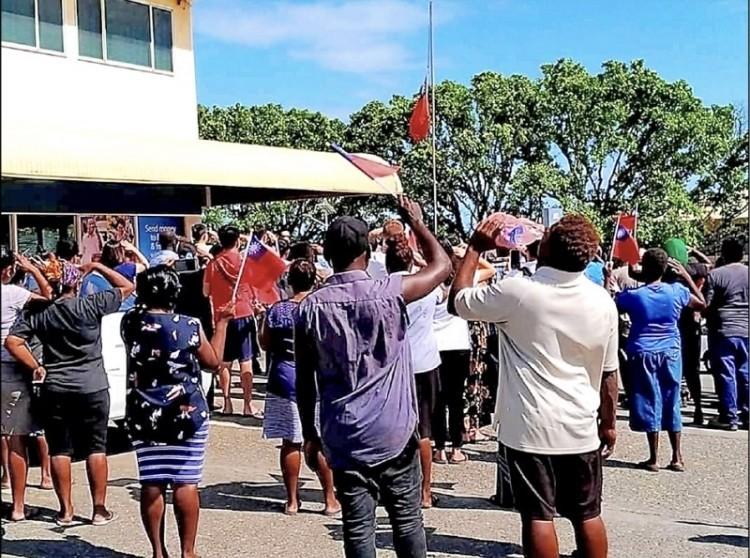 駐索羅門大使館在台索斷交隔日舉行降旗,索國人民聚集在現場向我國國旗致敬。(圖擷取自「我來自荷尼阿拉」臉書專頁)