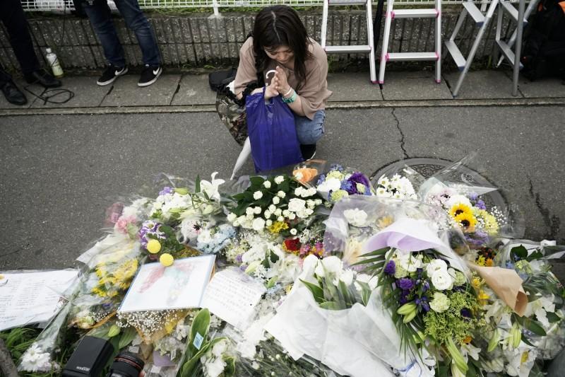 「京都動畫」發生縱火案,造成大量傷亡,一名女性今天前往現場獻花悼念。(美聯社)