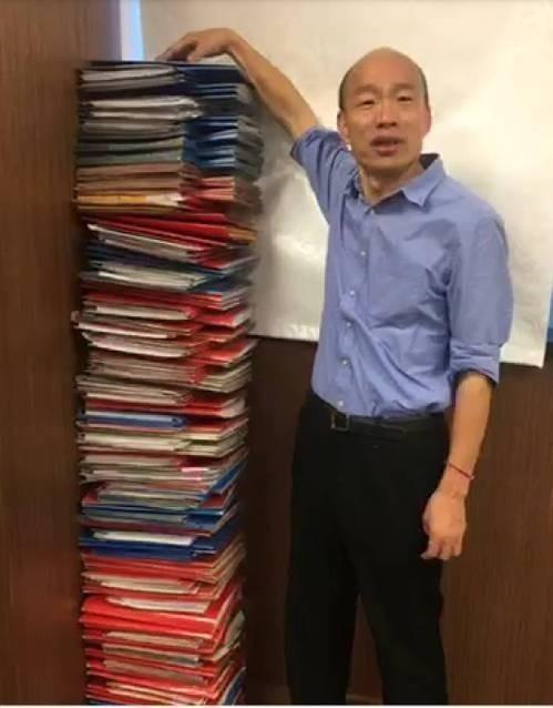 韓國瑜今曬出自己要批閱的公文累積有「這麼高」,快要比自己的身高還要高了。(圖擷取自臉書_韓國瑜)
