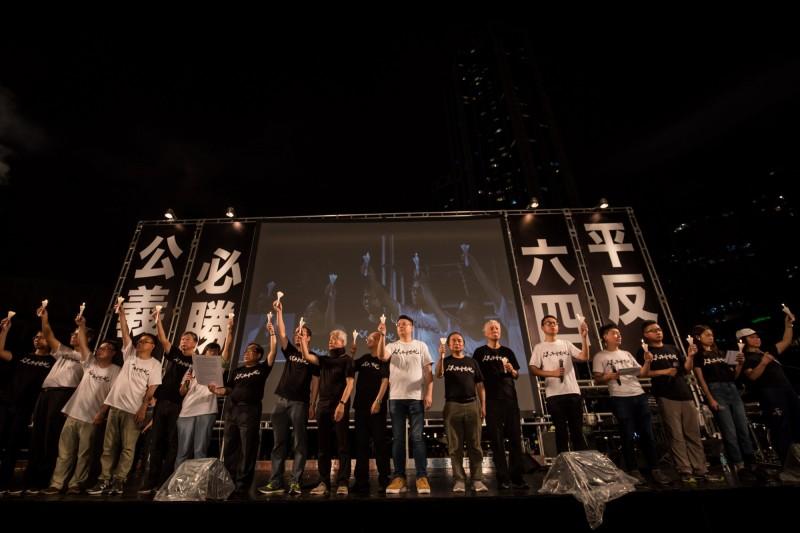 香港支聯會成員、「佔中三子」朱耀明(右6)出席晚會上台發言,他呼籲大家以愛、以良善、以公義對抗不義的政權。(彭博)