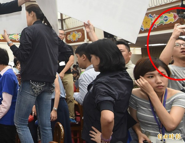 有一名身穿灰衣服的不名男子(紅圈處)混在國民黨立委中,跟著丟水球。(資料照,記者廖振輝攝)