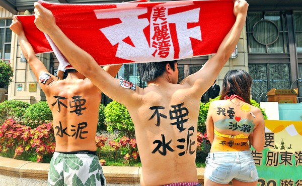 "Protesters in front of the Miramar Garden Hotel in Taipei on April 17 last year hold towels bearing the slogan ""Demolish the Miramar Resort,"" referring to an unfinished beachfront development in Taitung County. Photo: Chang Chia-ming, Taipei Times"
