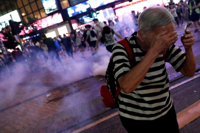 香港一個化學工程師團隊研究指出,催淚煙可殘留在環境中長達3週。圖為8日港警於銅鑼灣街頭施放催淚彈,一名婦人連忙走避。(路透)