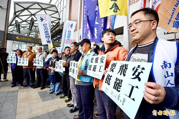 Representatives of various labor unions hold signs at Taipei International Airport (Songshan Airport) yesterday to express their support for China Airlines pilots who are on strike. Photo: Peter Lo, Taipei Times