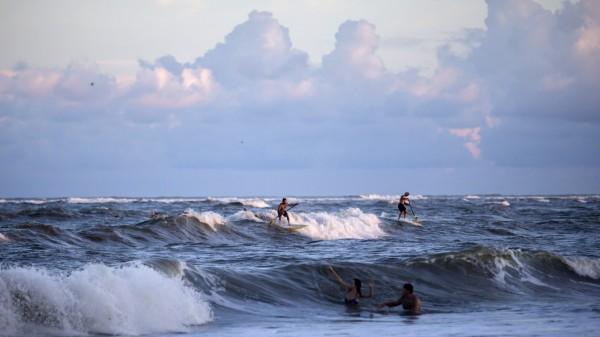 仍有不少美國民眾在海邊戲水。(美聯社)