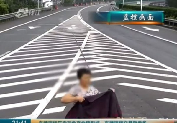 有中國大媽因擔心違規倒車被拍,竟下車用衣服遮住監視器。(圖擷取自影片)