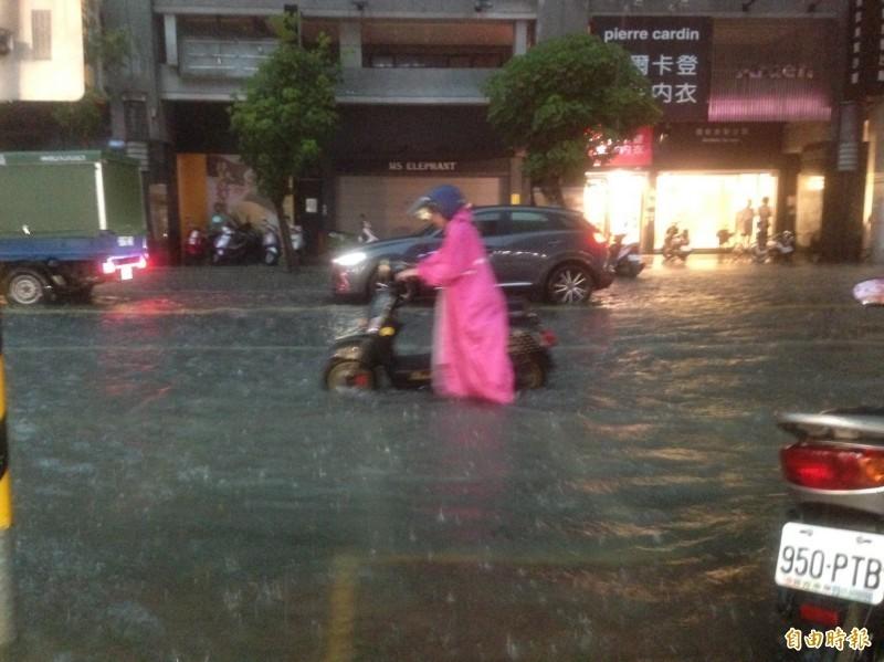 豪大雨今下午狂襲高雄市區,瑞豐夜市鄰近道路積水淹上人行道,多輛機車拋錨,女騎士呼救「發不動啦」。(記者黃旭磊攝)