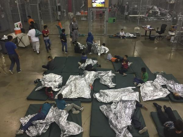 德州麥卡倫拘留非法移民的設施,一個鐵籠內關著約20名孩童,他們用錫箔紙當棉被取暖。(法新社)
