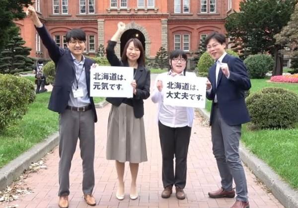 日本民眾手上拿著字卡告訴大家北海道很好、沒問題。(影片截圖由臉書粉專「台灣女孩的北海道生活」提供)