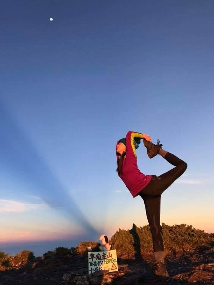 何茜芸在卑南主山做出舞王動作時,與晨光映照,氣象萬千。(何茜芸提供)