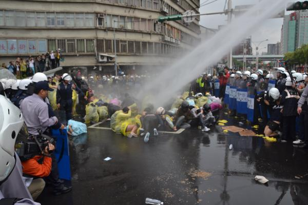 警方多次水柱強力攻擊靜坐群眾,噴完水後迅速上前拉人。(記者吳柏軒攝)